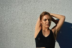 Waist up portrait of attractive young European sportswoman wearing black sports bra stretching muscles after cardio workout outdoors. Sports, vitality, energy, wellness and physical exercise