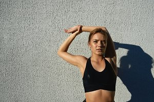 Outdoor portrait of confident young female runner stretching her arms before training session in fresh air. Attractive blonde sportswoman with fit athletic body warming up, preparing muscles for run