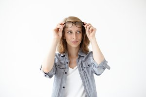 Picture of cheerful young woman dressed casually putting off her stylish eyeglasses in black frame and looking away with curious mysterious expression on her face. People and lifestyle concept