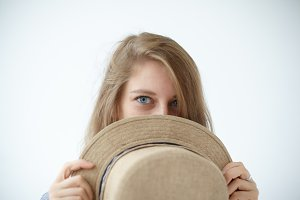 Portrait of cute strange mysterious young female model with enigmatic blue eyes covering face with round retro hat. Beautiful girl posing at white wall, peeking out from beige straw headwear