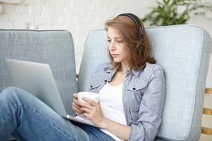 Candid shot of attractive young woman self-employed translator in black headphones translating video interview or online series sitting at grey couch in front of open laptop and drinking coffee or tea