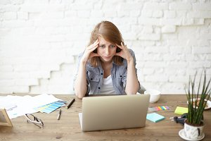 Unhappy depressed nervous young female worker dressed casually feeling panic and frustrated touching her face while having computer problem after she accidentally deleted report that she just finished