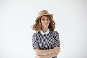 People, style and fashion concept. Isolated picture of attractive joyful young woman wearing summer straw hat and retro dress posing in studio with arms folded, her hair streaming in the air