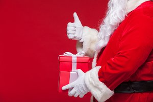 christmas Photo of Santa Claus gloved hand with red giftbox. thumb up