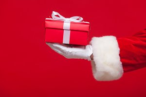 christmas Photo of Santa Claus gloved hand with red giftbox