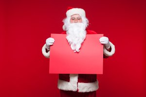 Santa Claus pointing in blank advertisement banner isolated on red background with copy space red leaf