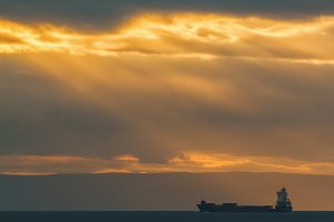 Container Cargo ship in the ocean at sunset sky, silhouette