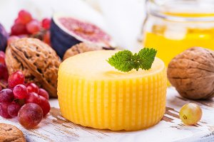 Wheel of yellow cheese with spices and snacks