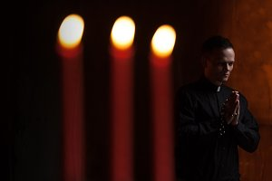 Portrait of handsome catholic priest or pastor with dog collar, dark red background.