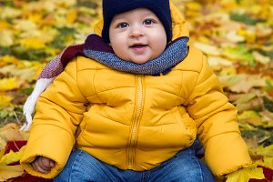 child in a yellow jacket and scarf and hat sitting on the ground