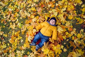 child in a yellow jacket and scarf and hat lies on the ground