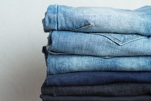 a stack of different colors jeans