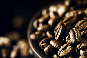Tasty coffee beans in bowl on table