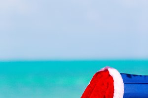 Sun lounger with Santa Hat at beautiful tropical beach with white sand and turquoise water. Perfect Christmas vacation