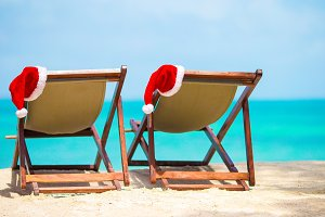 Sun loungers with Santa Hat at beautiful tropical beach with white sand and turquoise water. Perfect Christmas vacation