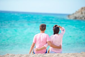 Young family of two on white beach during summer vacation