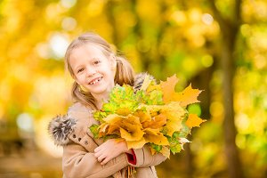 Portrait of adorable little girl with yellow leaves bouquet in fall at beautiful autumn day