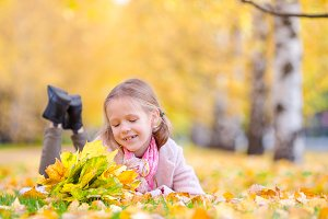 Portrait of adorable little girl with yellow leaves bouquet in fall. Beautiful smiling kid lying on leaves carpet