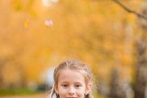 Portrait of adorable little girl with yellow leaves bouquet in fall