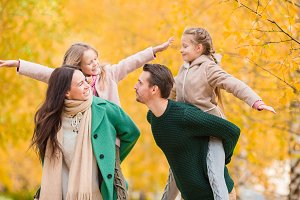 Beautiful happy family of four in autumn day outdoors