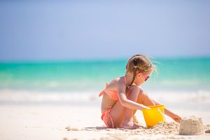 Little girl at tropical white beach making sand castle