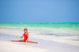 Active little girl on white beach having fun