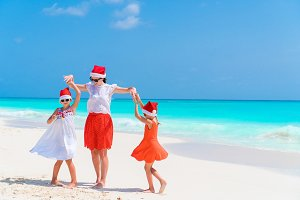 Happy beautiful family of mom and kids in red Santa hats on a tropical beach celebrating Christmas