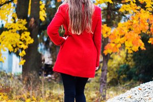 The girl in a red coat stands in a yellow autumn park