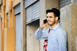 young man of style hipster fashion talking on mobile phone