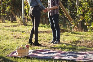 Couple holding hands and standing in apple orchard