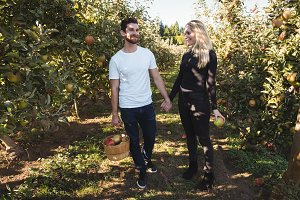 Happy couple holding hands and standing in apple orchard