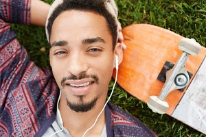 Restful carefree teenage boy with trendy mustache and beard lies at green lawn near his skateboard, listens audio tracks, rests after active day. Male skater enjoys music. Active lifestyle concept