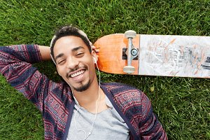 People, leisure and lifestyle concept. Smiling joyful skater rests after training, lies on green grass near skateboard, grins at camera, enjoys music in earphones uses some electronic device