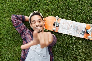 Horizontal portrait of joyful bearded male skateboarder lies on green grass near skateboard, listens to music with earphones, points at you, chooses something. Film effect and selective focus