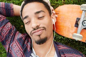 People and enjoyment concept. Close up of bearded stylish male closes eyes with pleasure, listens to favourite song in white earphones, rests on green lawn near skateboard, enjoys good atmosphere