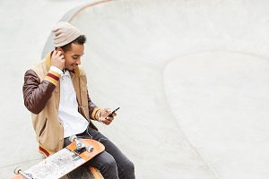 Urban stylish hipster guy sits near his skateboard, wears trendy clothes, makes video call on mobile phones, uses hands free, talks with friends, invites him to go in for sport together next day