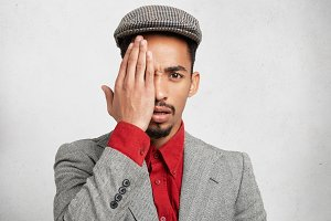 Portrait of attractive male wears cap, formal red shirt with jacket, covers eye with hand as conceals big bruise. Mixed race young macho man hides half of face, stands against white background