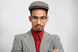 Close up portrait of confident serious man has dark beard and mustache, wears trendy spectacles, red shirt and jacket, looks seriously at camera, demands explanation from someone who made mistake