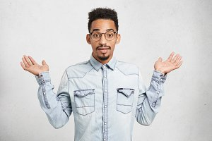 Cropped shot of fashionable young male wears denim clothes and glasses, gestures with hands, says: who cares, I don`t know anything, has indignant expression, poses at white studio background.