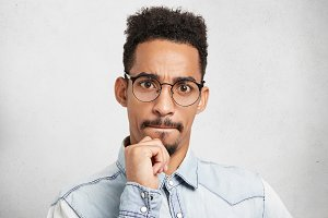 Portrait of mixed race serious focused bearded man with Afro hairstyle, keeps hand on chin, pressses lips, listens attentively someone talk or presentation, isolated over white studio background