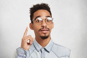 I get great idea. Confident mixed race male scientist wears roung glasses, has mustache and beard, raises finger up, develops new strategy of work, has inspiration and new interesting thoughts