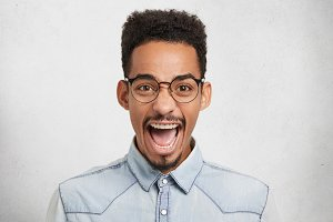 Emotional African American male in round spectacles, opens mouth in excitement, exclaims joyfully, being glad to win competition, celebrates triumph and victory. Successful businesman feels devour