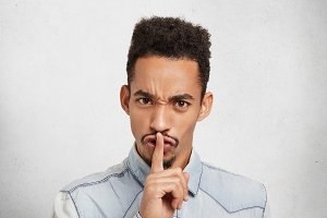 Serious dark skinned man makes silence gesture, says shh, asks to be quiet as there is exam in next room. African American young man with mustache makes request to be mute, keeps fore finger on lips