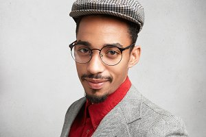 Confident male student wears spectacles, cap and jacket, has serious expression, worries before final exam. Intelligent man with mustache and beard poses in white studio. People, style concept