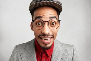 Close up portrait of clumsy comic male wears big spectacles, cap and jacket, smiles with surprisment, looks with bugged eyes, being astonished to hear unexpected news or see gift from friend