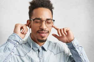 Horizontal portrait of dark skinned stylish male with Afro hairstyle, closes eyes in enjoyment, listens favourite audio track, being relaxed. Pleasant looking man uses headphones for entertainment