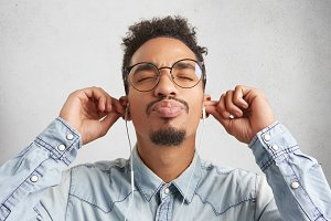 Close up portrait of Afro American man with moustache and beard wears denim shirt and round big glasses, closes eyes with enjoyment as listens to audio track in earphones, isolated on white background