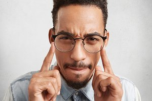 Indoor shot of hipster guy in round spectacles keeps fingers on temples, tries to concentrate and find right solution or way out in difficult situation, isolated over white studio background