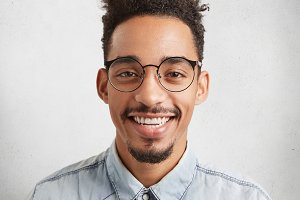 Close up portrait of cheerful dark skinned male with mustach and beard, smiles happily, wears denim shirt, being glad to pass exams successfuly, recieves praise from professor. Happiness concept