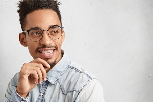 Intelligent clever male student wears round spectacles, thinks over future project, looks thoughtfully aside stand over white background with copy space for your advertisment or promotional text